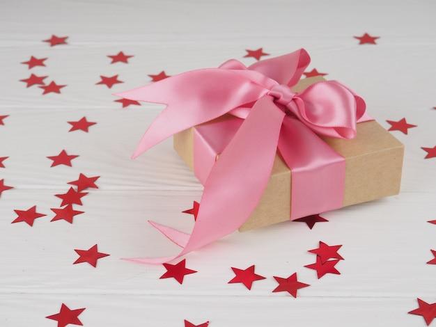 Giftdoos met helder rood roze lint op witte achtergrond met sterren