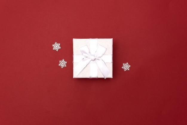 Giftdoos met kegels op een rode achtergrond. kerst achtergrond. bovenaanzicht ruimte voor tekst.