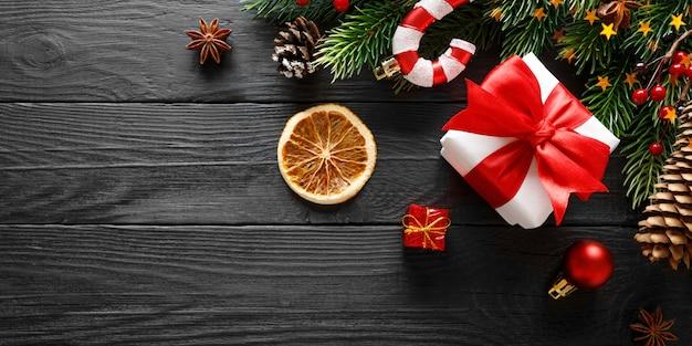 Giftdoos met kerstmisdecoratie op zwarte houten achtergrond