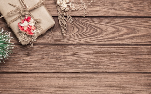 Giftdozen en minikerstboom op houten achtergrond