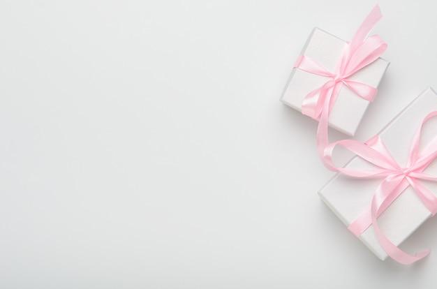 Giftdozen met roze lint op witte achtergrond.