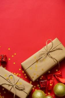 Giften en gouden kerstballen op een rode achtergrond.