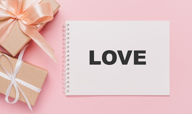 Giften met notitiebrief op geïsoleerde roze achtergrond, liefde en valentijnskaartconcept met tekstliefde