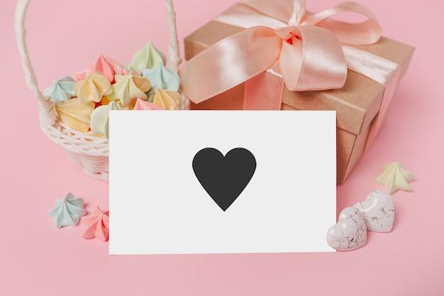 Giften met notitiebrief op geïsoleerde roze achtergrond met snoep, liefde en valentijnskaartconcept met hart