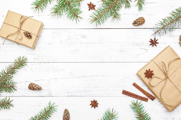 Giften voor nieuw jaar die in ambachtdocument dichtbij nette takken en kegels worden verpakt op witte houten hoogste mening als achtergrond copyspace
