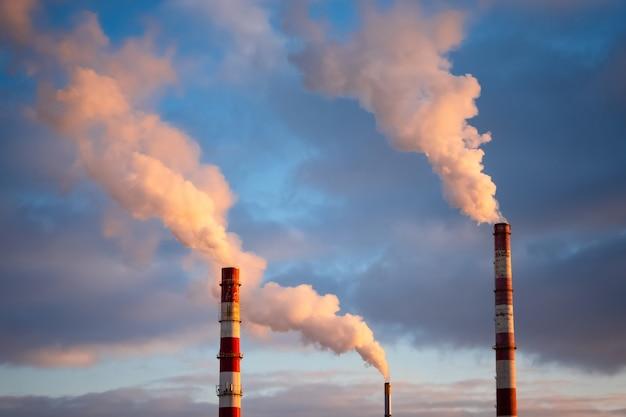 Giftige rookwolken die bij zonsondergang uit fabrieksschoorsteen komen. luchtvervuiling en opwarming van de aarde veroorzaakt door oude industriële energiecentrale
