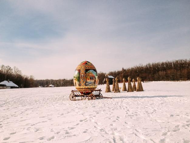 Gigantische decoratieve eieren met ornament op een slee in de sneeuw