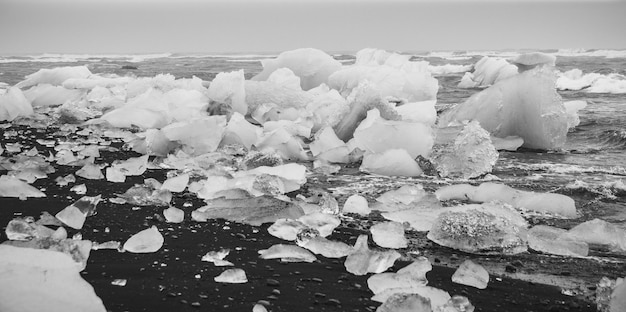 Gigantische ijsblokken die losstaan van ijsbergen aan de kust van een ijslands strand.