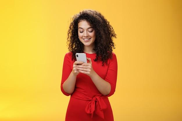 Gil die een bericht verzendt, verspreidt nieuws over een sociaal netwerk met een feest dat vrienden uitnodigt via een smartphone die de mobiele telefoon in handen houdt en breed glimlacht op het apparaatscherm als poserend over een gele achtergrond.