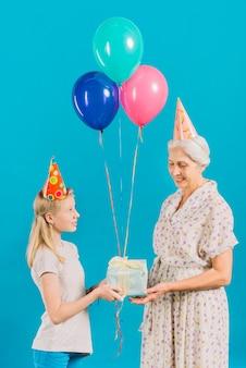 Gil die verjaardagsgift geeft aan haar grootmoeder op blauwe achtergrond