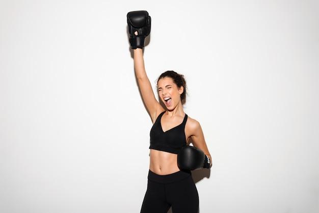 Gillende donkerbruine geschiktheidsvrouw in bokshandschoenen met hand lucht