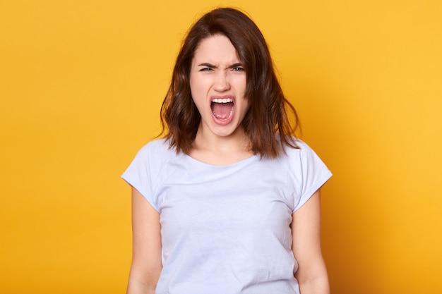 Gillende emotionele boze vrouw die over gele studio wordt geïsoleerd