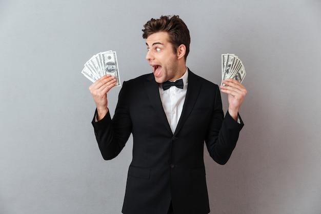 Gillende gelukkige mens in het officiële geld van de kostuumholding.