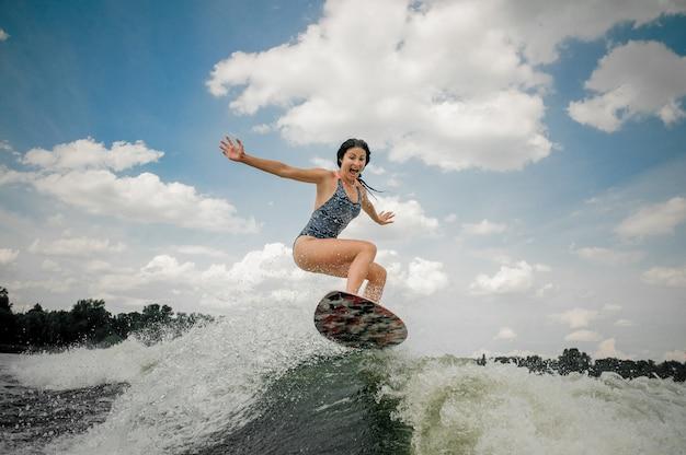 Gillende jonge vrouw die op het bord springt wakesurfing op de rivier