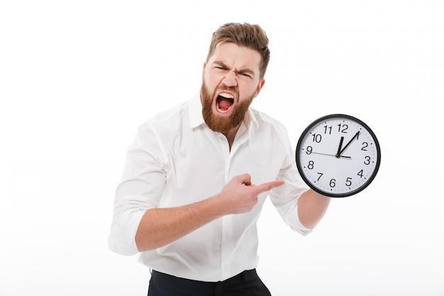 Gillende mens in bedrijfskleren die en op klok houden richten
