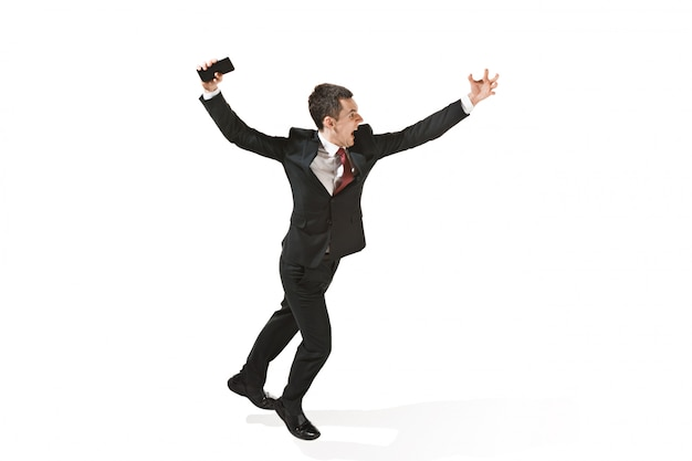 Gillende zakenman die met mobiele telefoon over witte studio loopt
