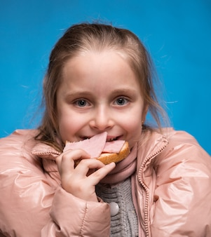 Gilr die sandwich met ham op een blauwe achtergrond eet