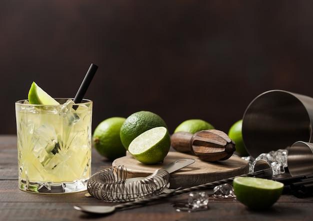 Gimlet kamikaze-cocktail in kristalglas met limoenplak en ijs op houten oppervlak met verse limoenen en zeef met shaker.