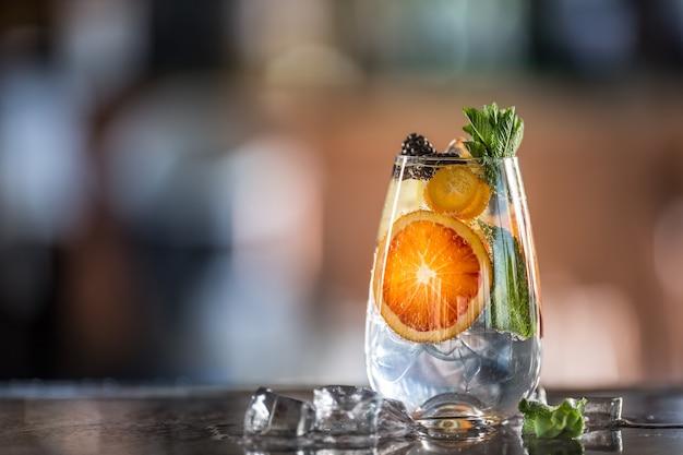 Gin tonic cocktail met vers tropisch fruit op toog in pup of restaurant.