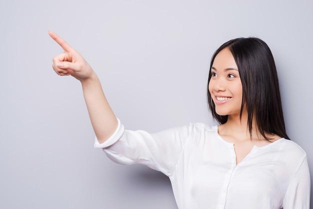 Ginder! mooie jonge aziatische vrouw die wegwijst en glimlacht terwijl ze tegen een grijze achtergrond staat