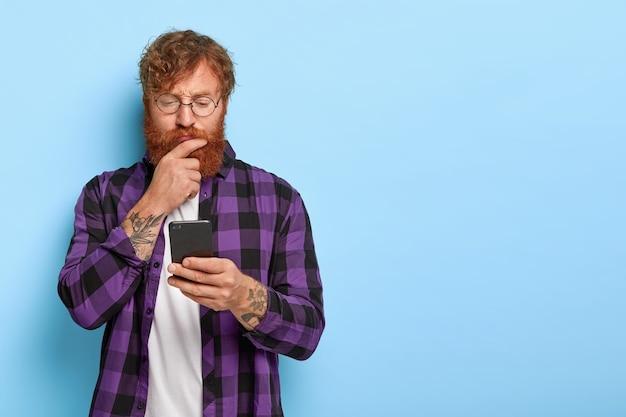 Ginger millennial guy gebruikt mobiele telefoon applicatie voor het synchroniseren van gegevens, heeft een serieuze blik, draagt een ronde bril