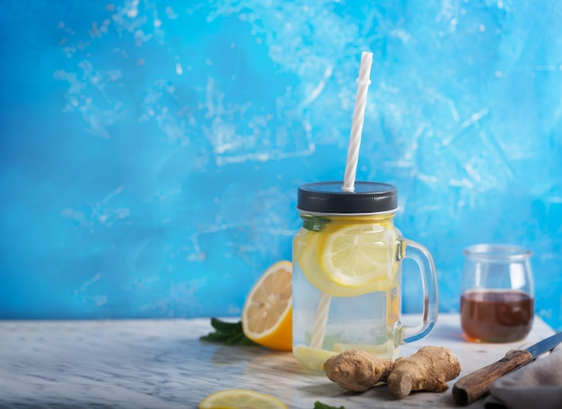Ginger water in glazen pot met citroen en honing op blauwe tafel met kopie ruimte
