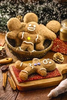 Gingerbread man wordt bedekt met kleurrijk glazuur, versierd kersteten, zelfgemaakte kerstkoekjes