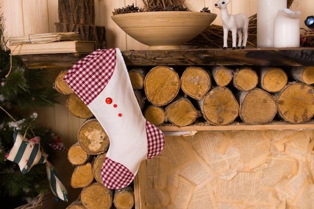 Gingham kerstsok hangend aan rustieke houten schoorsteenmantel fire