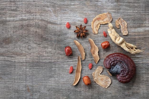 Ginseng, lingzhi-paddenstoel, gojibes, rode jujube en thee op een oud hout. bovenaanzicht