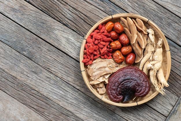 Ginseng, lingzhi-paddenstoel, gojibes, rode jujube en thee op hout. bovenaanzicht