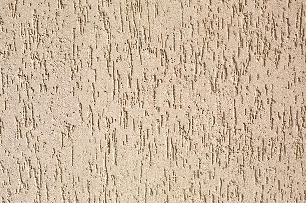 Gips op de muur met een schorskeverpatroon van beige en zandkleur. achtergrond, textuur.