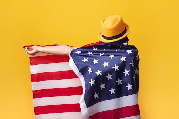 Gir met amerikaanse vlag over gele achtergrond, meisje in modieuze hoed met vlag van de v.s