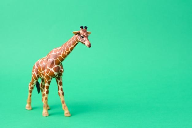 Girafstuk speelgoed op groene achtergrond wordt geïsoleerd die