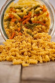 Girandole pasta gemorst uit glazen pot op houten achtergrond