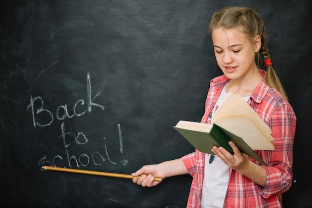 Girl holding book pointer standing