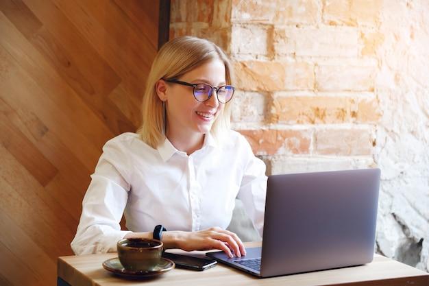 Girl manager, freelancer, zakelijke dame die op een laptop in een café werkt of samenwerkt.