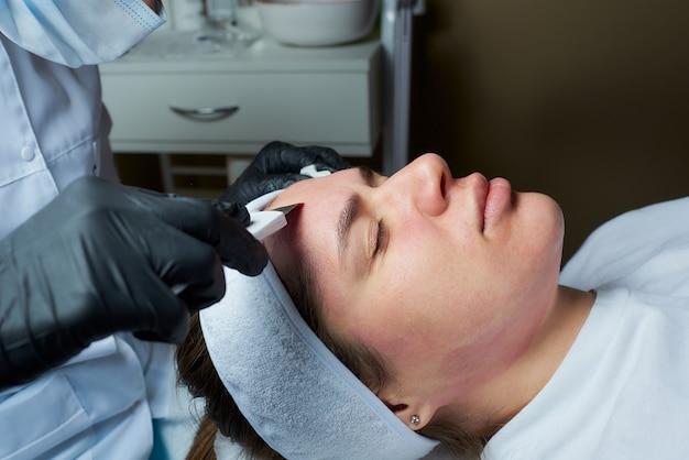 Girl's gezicht na een verwarmende lotion tijdens een ultrasone procedure in het cosmetologiebureau