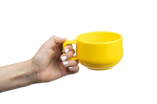 Girl's hand met gele thee beker geïsoleerd op wit. hand met de afwas.