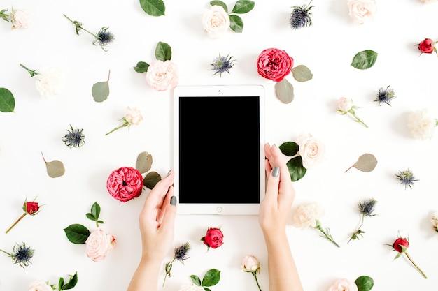 Girl's handen met tablet op floral frame met rode en beige roze bloemknoppen op wit