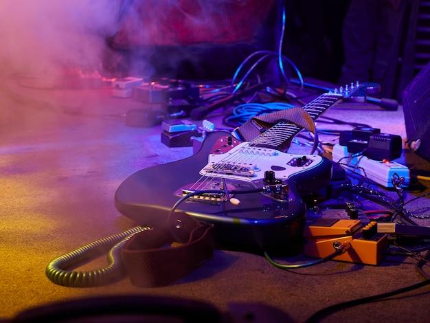 Gitaar en gitaarapparatuur liggen op het podium in mist en rook in paarse, blauwe en oranje verlichting.