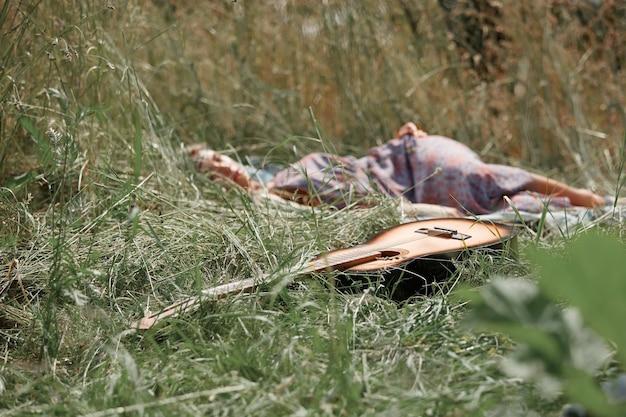 Gitaar en slapende hippie meisje in de natuur op zomerdag
