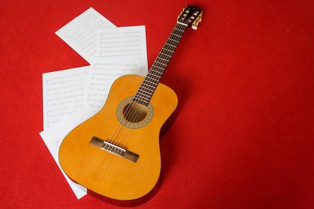 Gitaar met muziekblad op rode vloer. samenvatting en kunstachtergrond met exemplaarruimte.