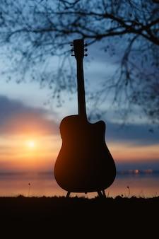 Gitaar silhouet bij zonsondergang.