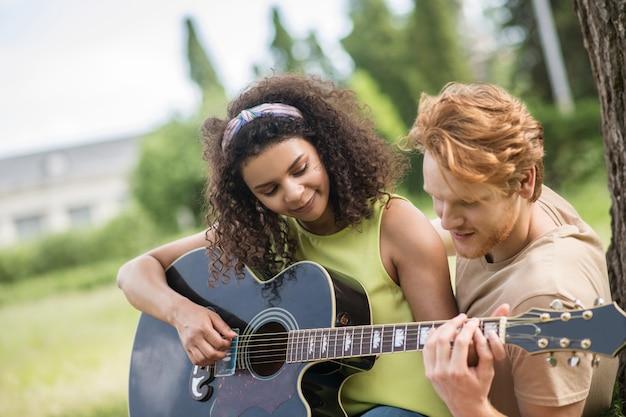 Gitaar spelen. jonge zorgzame roodharige man die zijn lachende, krullende vriendin leert gitaar te spelen in het park op een mooie dag
