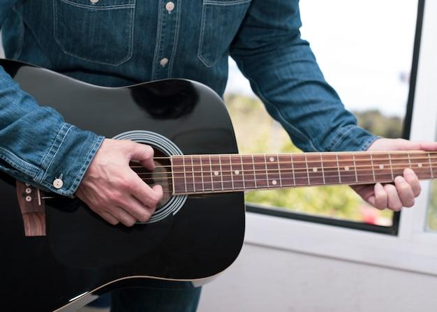 Gitaarles of twee samen spelende muzikanten, van achter een gitaar genomen