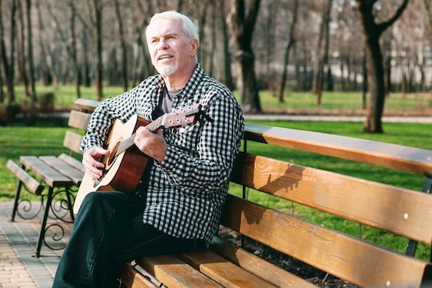 Gitaarsnoer. aangename volwassen man zingen en gitaar spelen