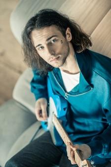 Gitaarspelen. knappe knappe kerel met blauwe ogen en zwarte stoppels die een heldere elektronische gitaar draagt