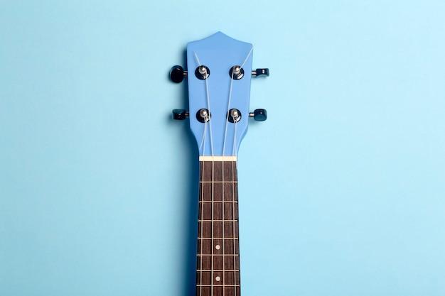 Gitaarukelele op een blauwe achtergrond. muziek spelen gitaar concept.
