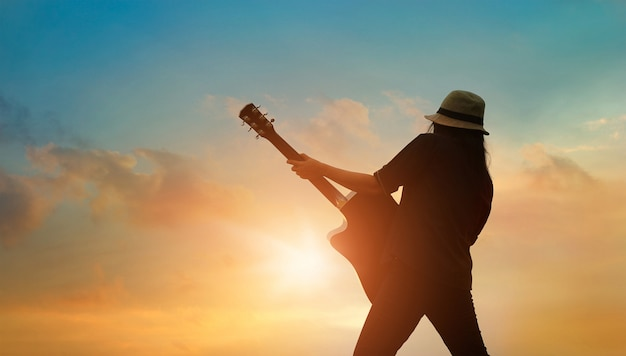Gitarist die akoestische gitaar op zonsondergang speelt