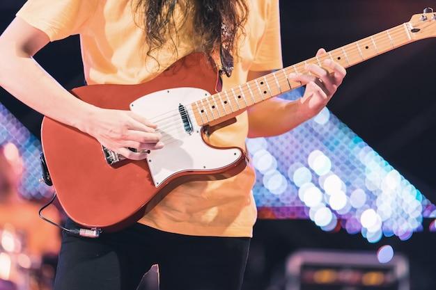 Gitarist die elektriciteitsgitaar op overlegstadium speelt. enterment en muziekconcept.